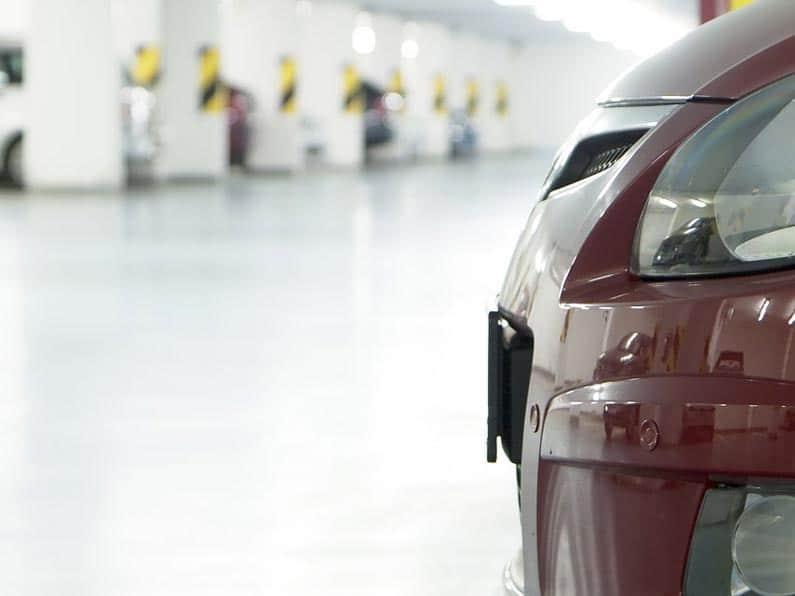 About Us: Parking Management - A dark red car parked in an underground parking